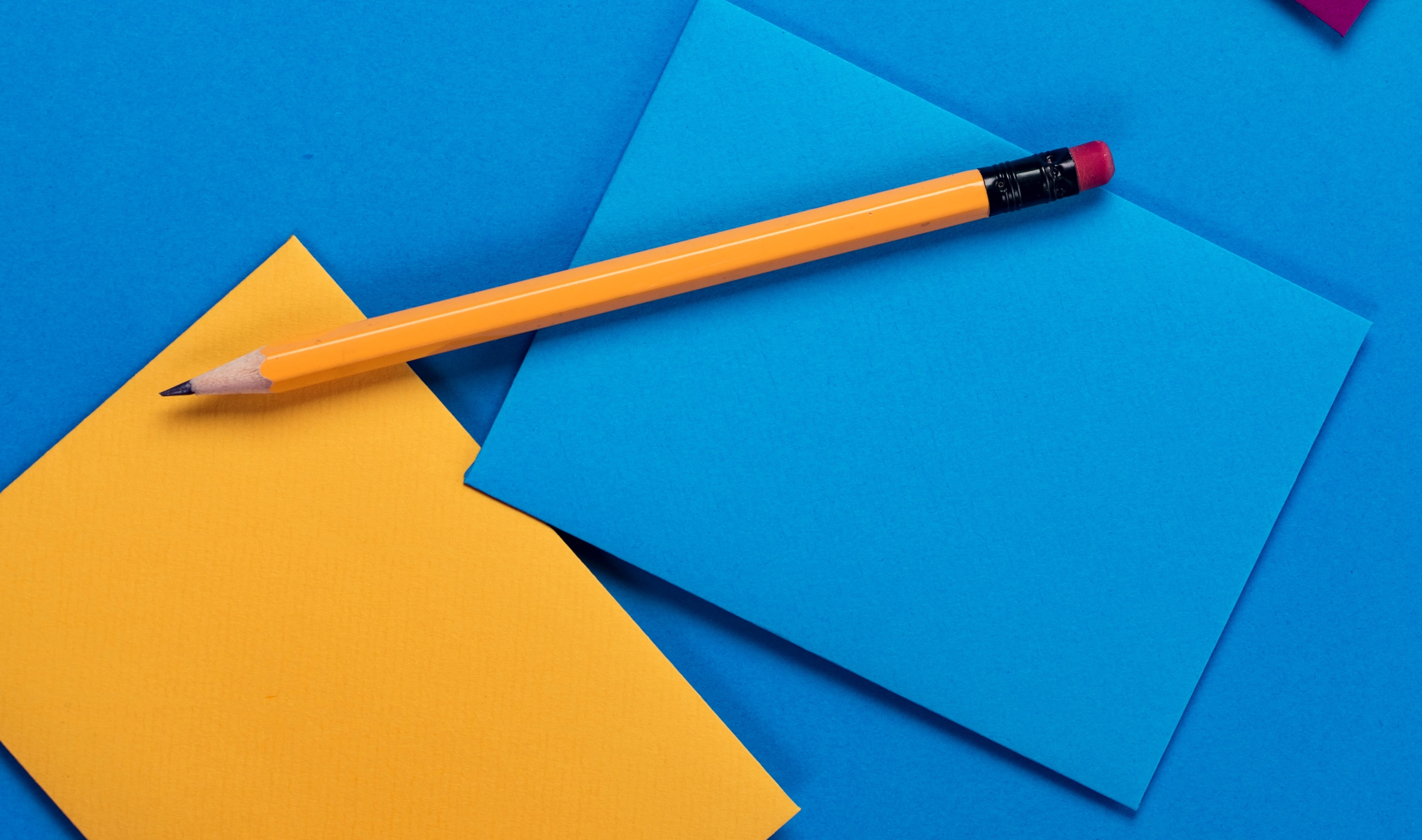 Yellow pencil with blue and yellow envelopes on a bright blue surface